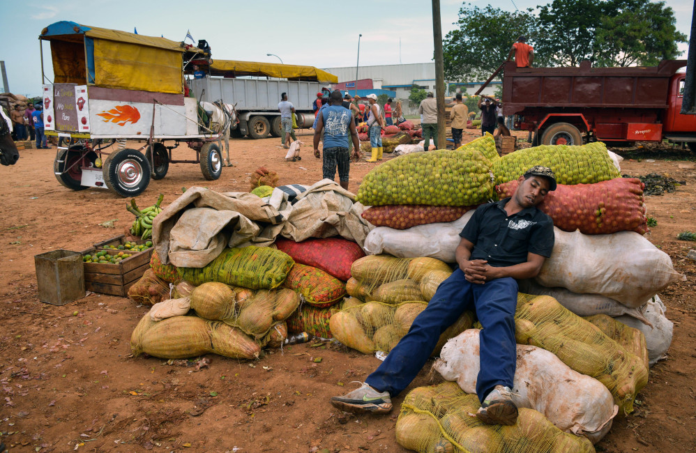 A fruit and vegetable farmer rests as he waits for buyers at a wholesale market in Havana.