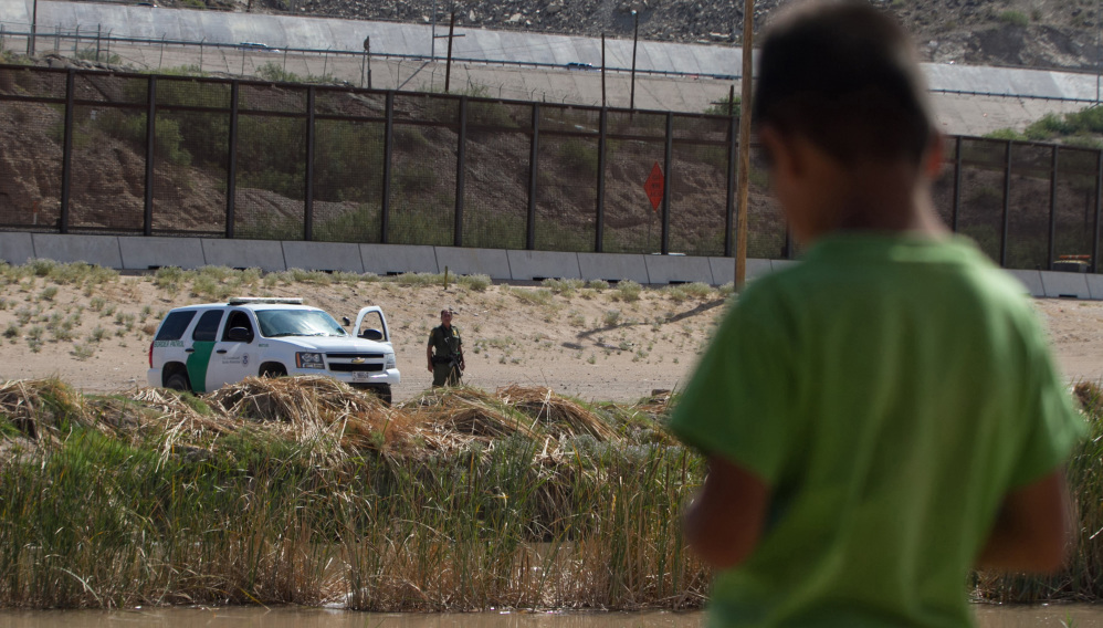 A Mexican boy looks at a member of the U.S. Border Patrol standing guard on the border between El Paso in the United States and Ciudad Juárez in Mexico, on July 22, 2014.
