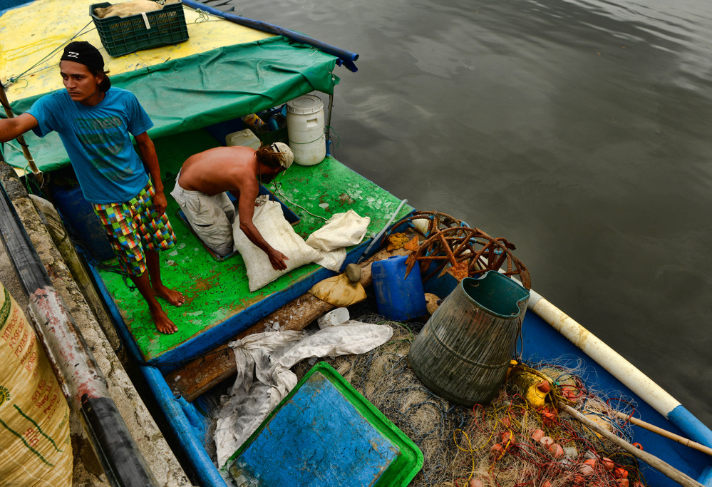 Fishermen load ice onto a longline boat at the Martec Industries dock in Quepos.