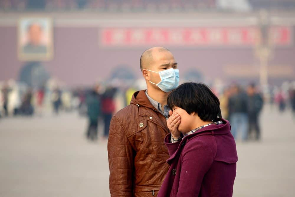 A man wears a face mask as another visitor covers her mouth during a visit to Tiananmen Square in Beijing on Nov. 5, 2013. China's top negotiator at international climate talks said that air pollution in his own country -- the world's biggest carbon emitter -- is harming its citizens.