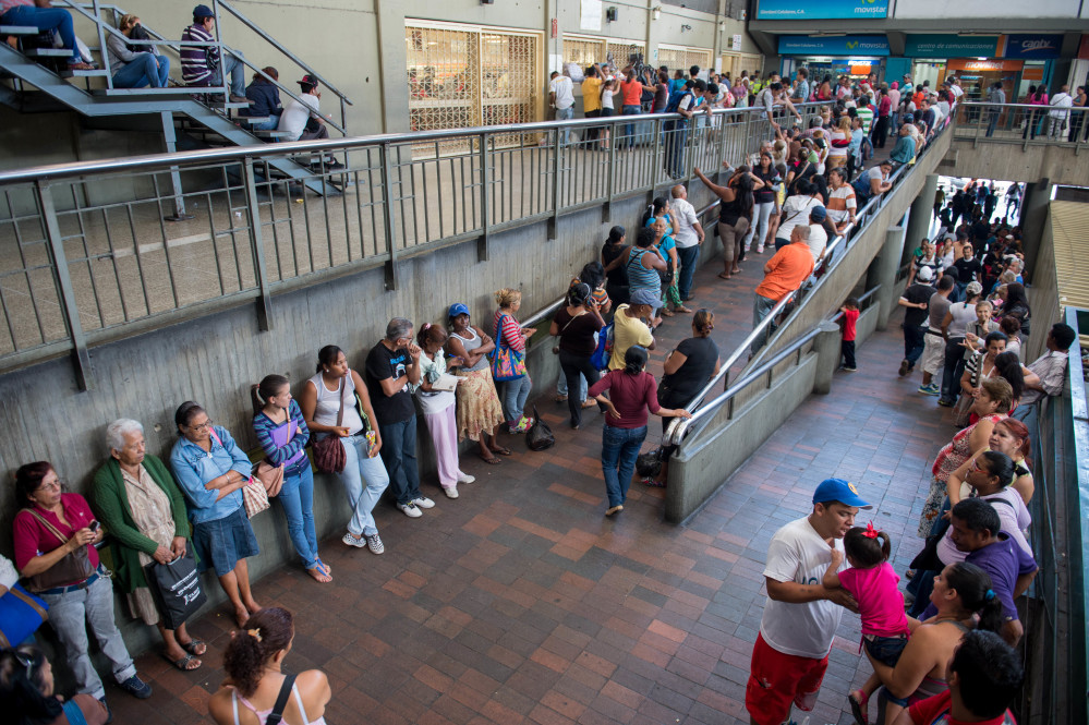 People queue up outside a supermarket in Caracas on Jan. 13, 2015.