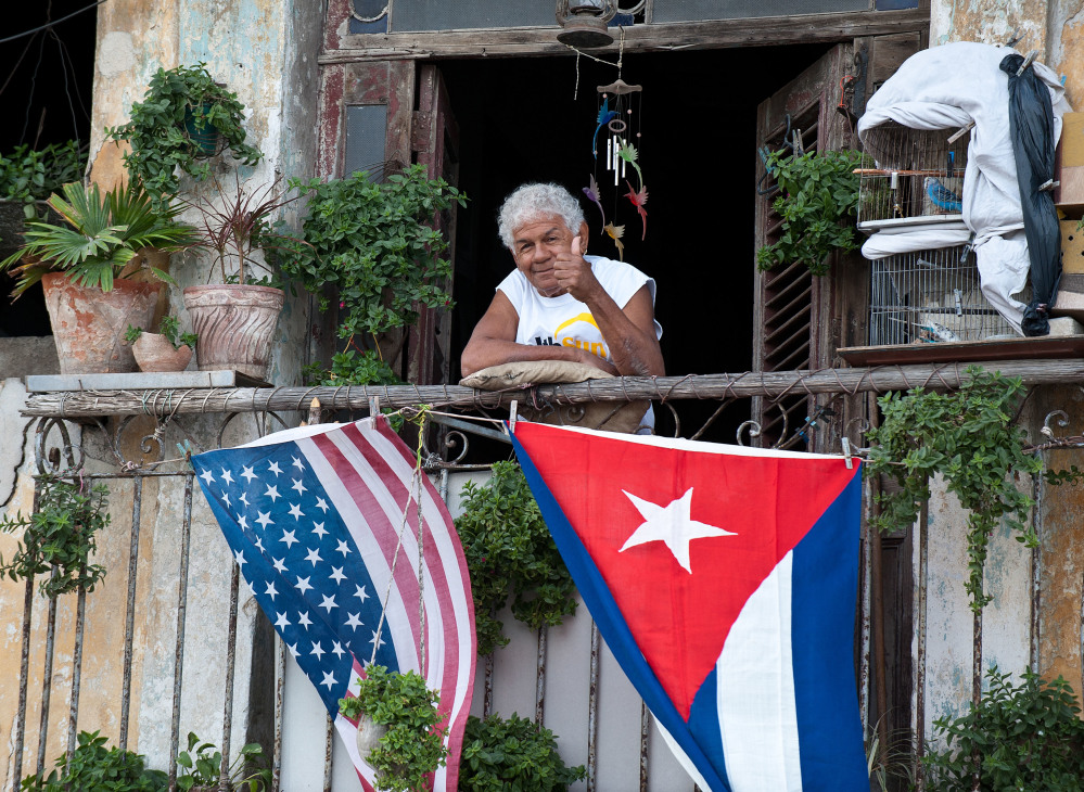 A Cuban gives the thumb's up from his balcony decorated with the U.S. and Cuban flags in Havana, on Jan. 16, 2015. The United States eased travel and trade restrictions with Cuba in January, marking the first concrete steps towards restoring normal ties with the Cold War-era foe since announcing a historic rapprochement.