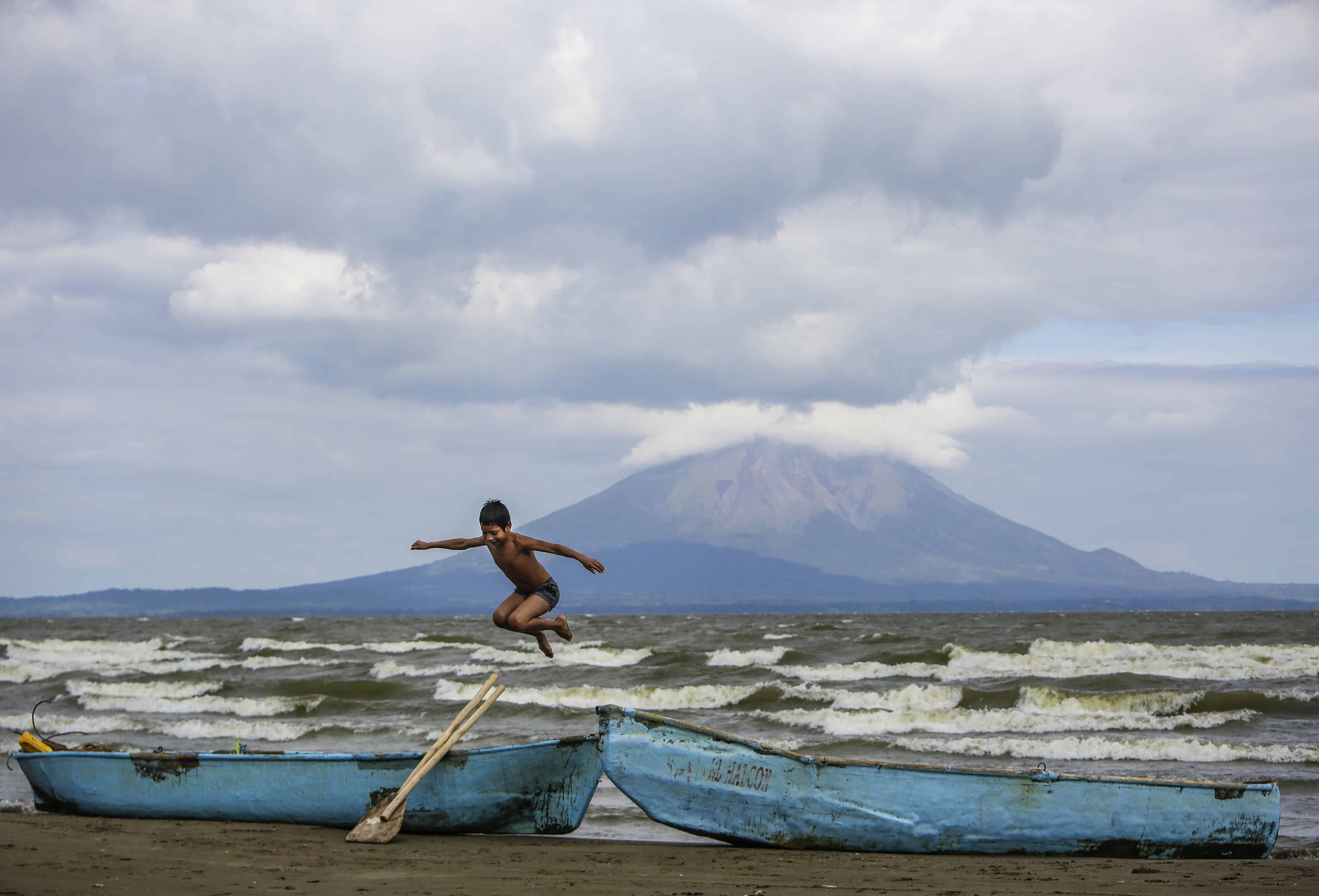 A young boy plays near two fishing boats along the shore of Lake Cocibolca in Rivas, Nicaragua.