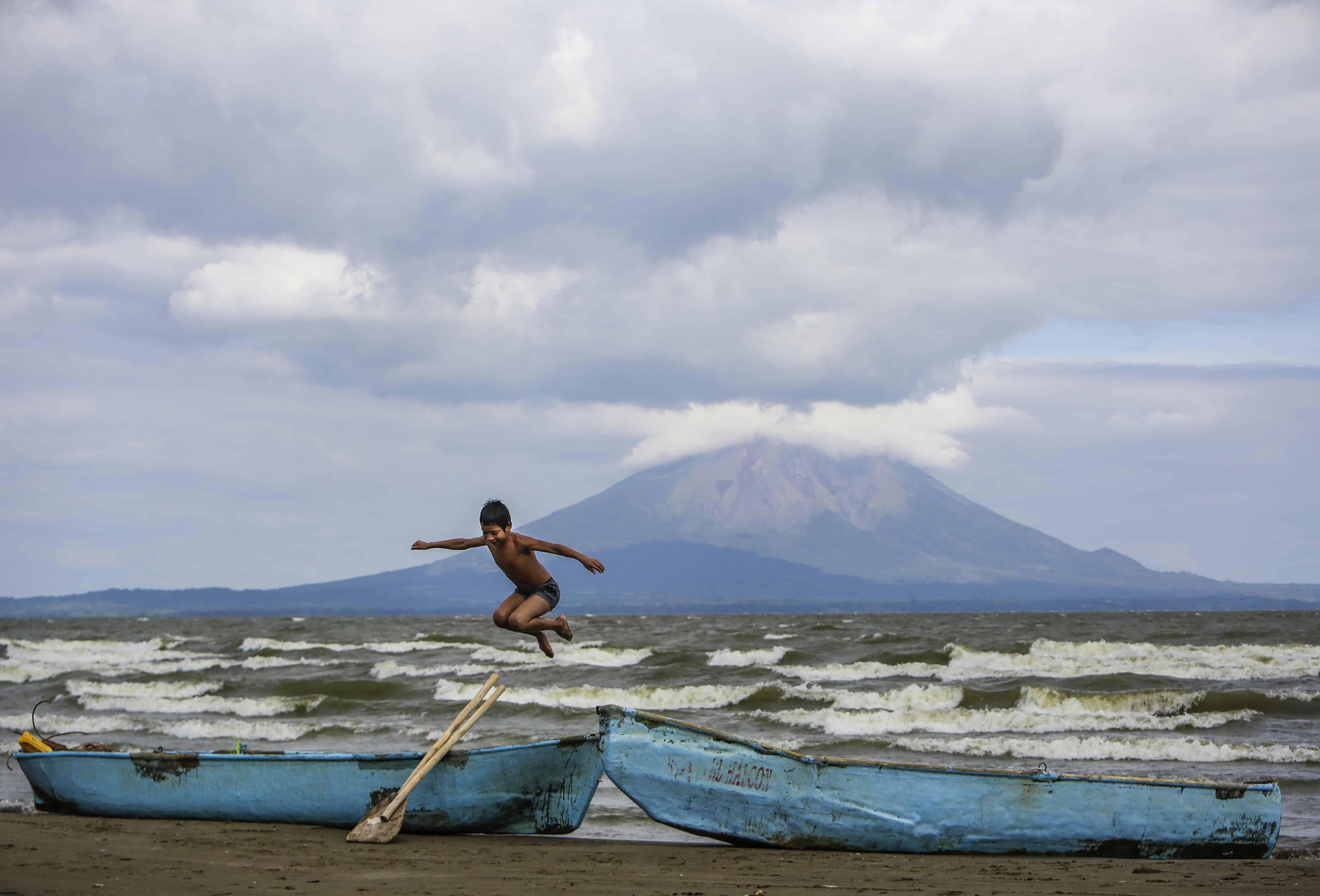 A young boy plays near two fishing boats along the shore of Lake Cocibolca in Rivas, Nicaragua.