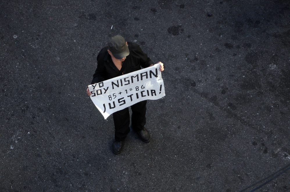 """A man holds a placard that reads """"I am Nisman, 85+1, Justice"""" during a rally in front of the headquarters of the AMIA (Argentine Israelite Mutual Association), in Buenos Aires on Jan. 21, 2015."""