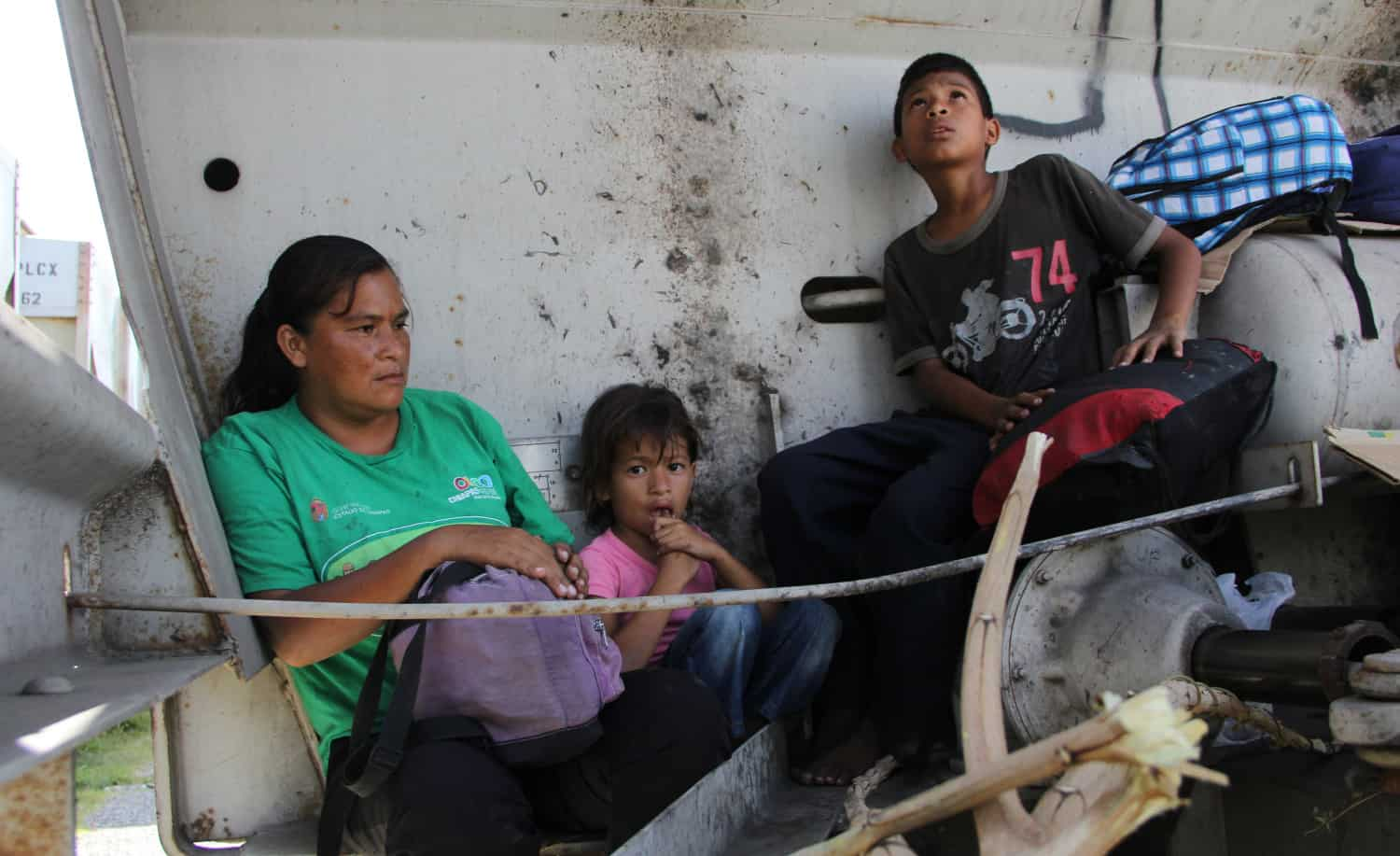 """A Central American immigrant and her children sit inside the so-called """"La Bestia"""" (The Beast) cargo train, in an attempt to reach the Mexico-U.S. border."""