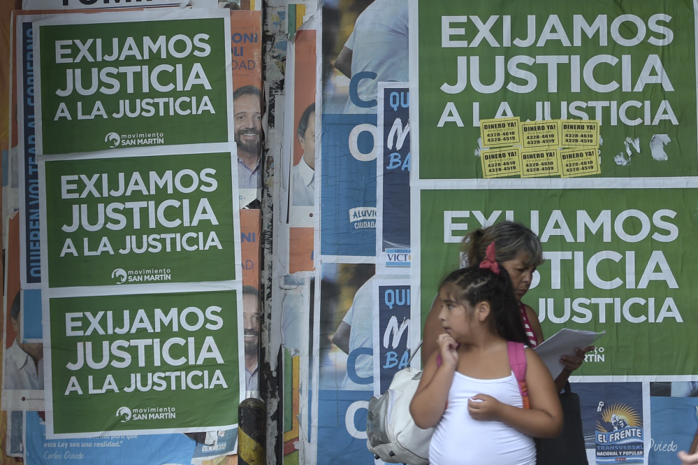 """People stand in front of posters reading """"We Demand Justice to the Justice"""" in Buenos Aires, on February 18, 2015 hours before a silent march to be led by prosecutors and opposition leaders -- over the mysterious death of a prosecutor who accused Argentina's President Cristina Fernandez de Kirchner of a cover-up in a 1994 bombing."""