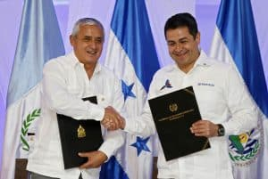 Honduran President Juan Orlando Hernandez (R) and his Guatemalan counterpart Otto Perez Molina as they shake hands after signing an intention letter of customs union during the first meeting of the Alliance for Prosperity of the North Triangle in Tela, Feb. 26, 2015.