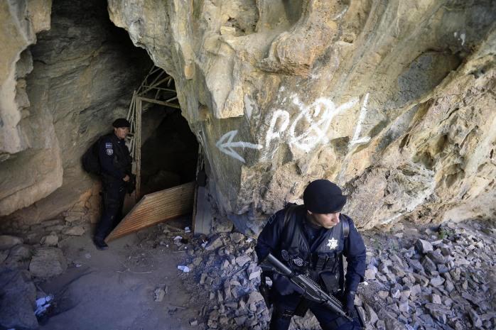 "Mexican federal police guard the entrance of a cave where Servando Gómez, aka ""La Tuta,"" had been hiding."