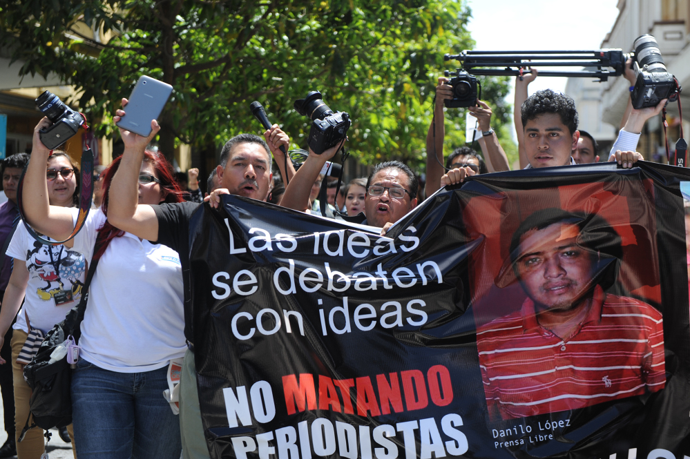 Guatemalan journalists carry a banner with the photos of two journalists killed on March 10 in an attack. Guatemala City, March 11, 2015.