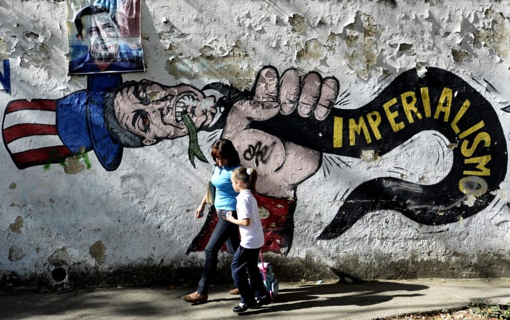 A woman and girl walk in front of a graffiti of Uncle Sam in Caracas on March 11, 2015.
