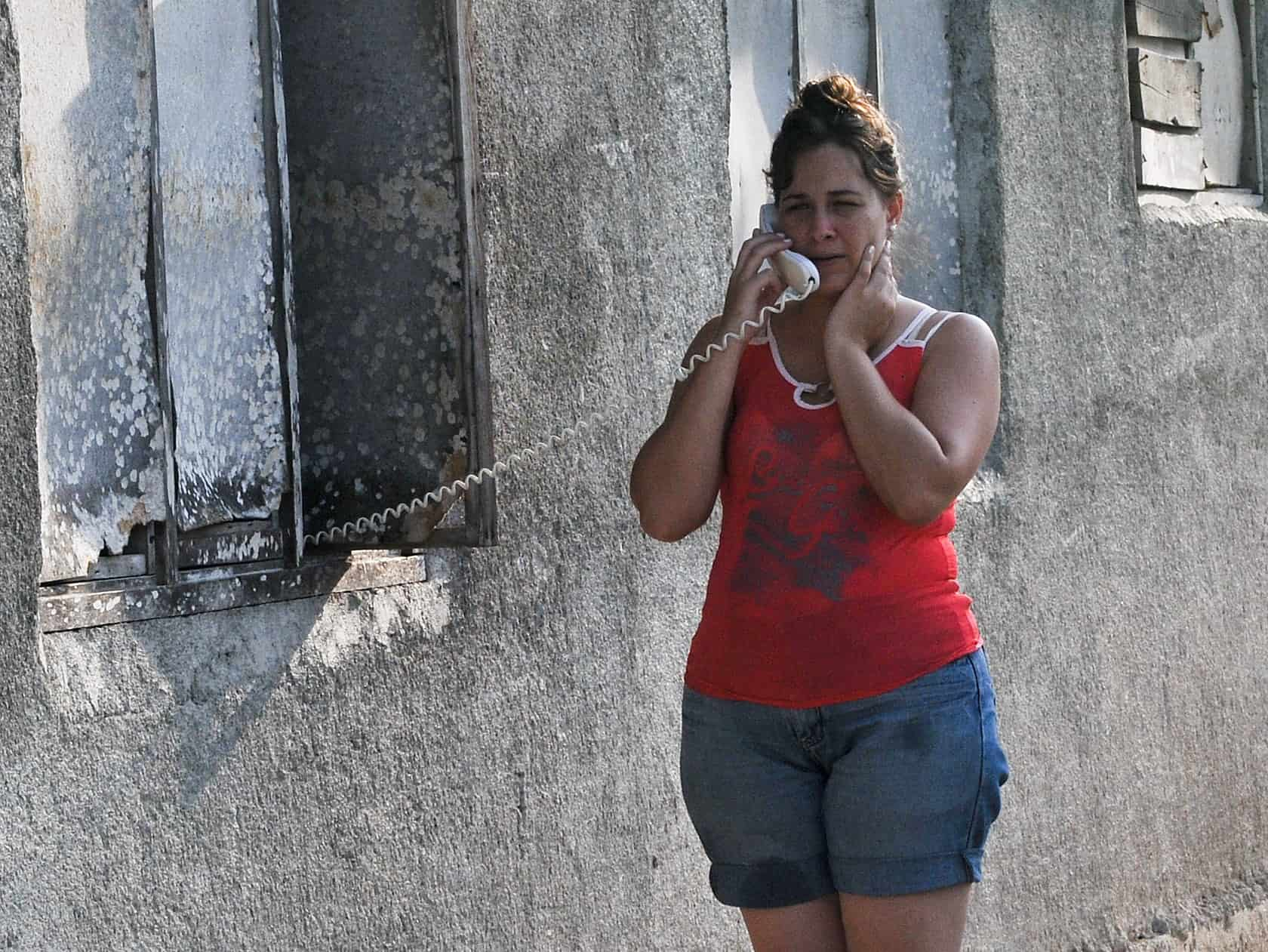 A Cuban woman talks on the phone on a Havana street.