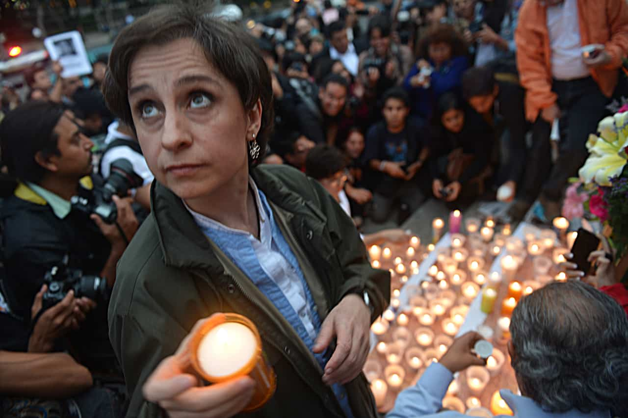 Mexican journalist Carmen Aristegui places a candle on an altar erected at the Independence Angel monument in Mexico City on May 5, 2012 during a vigil to protest against violence towards the press.