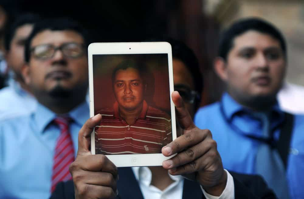 A Guatemalan journalist holds a picture of the late Danilo Lopez during a protest to condemn the armed attack that left two colleagues killed and another injured in the south of the country, in Guatemala City on March 11, 2015.