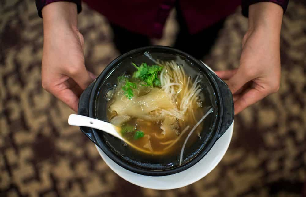 A waitress serves shark fin soup.