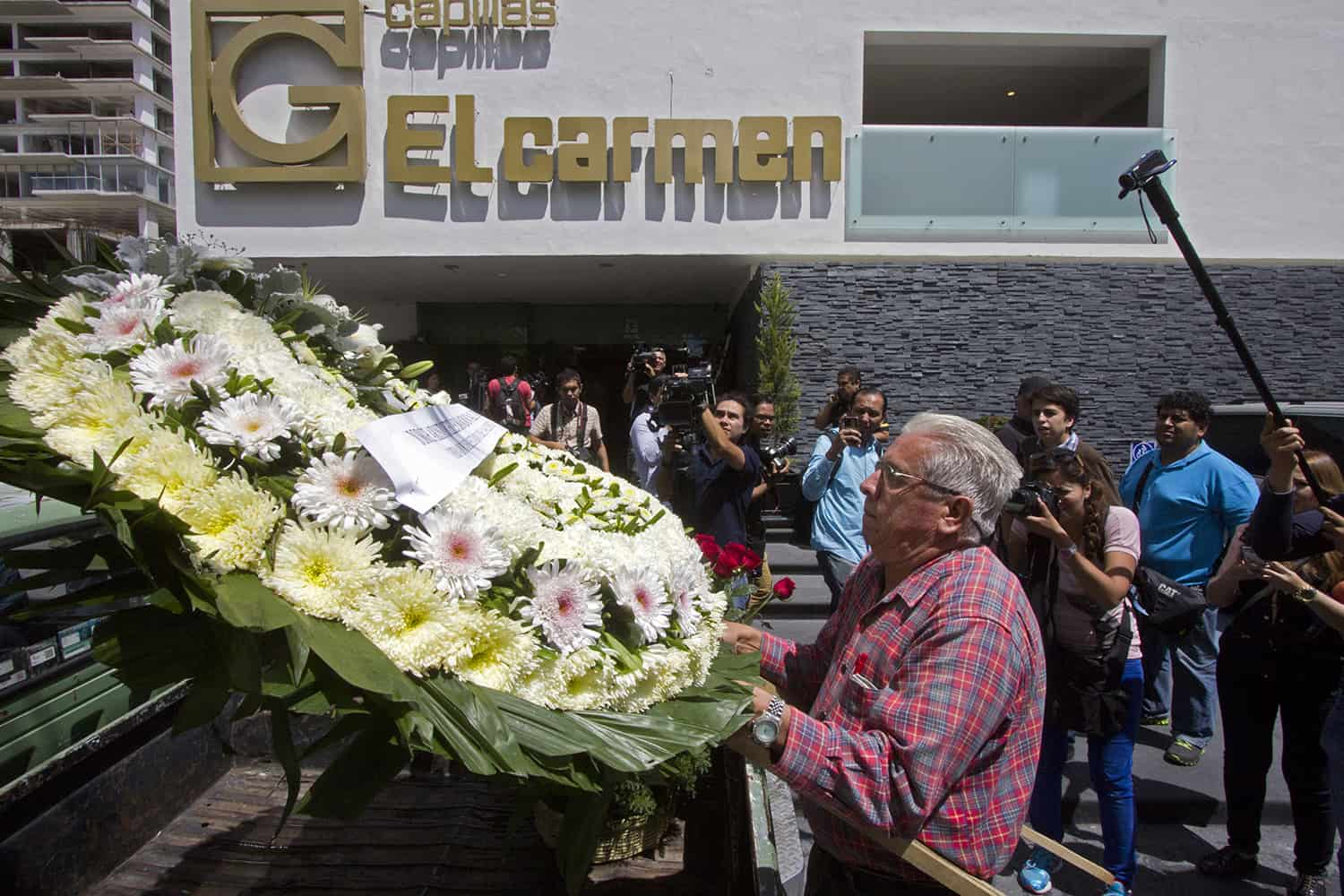 "A man delivers a wreath during the funeral of professional wrestler Pedro Aguayo Ramirez aka ""Perro Aguayo Jr"" in Guadalajara city on March 22, 2015."