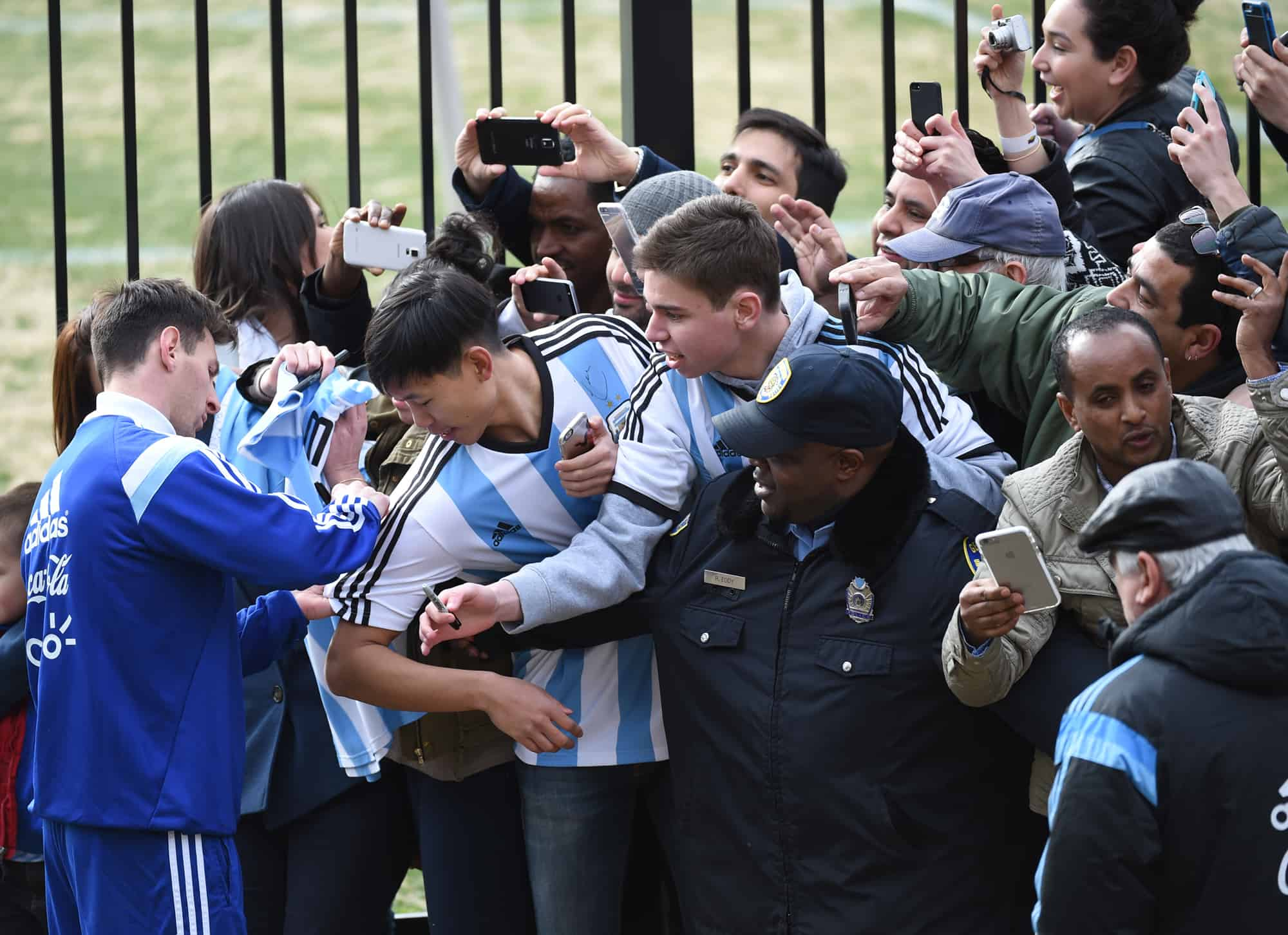 Lionel Messi, left, signs autographs for some of the hundreds of fans who showed up for a glimpse of the Argentine national team's practice at Georgetown University in Washington, March 24, 2015.
