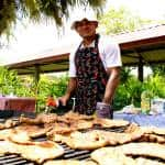 A cook overseas a grill full of steaks. All food served at the picnic was produced on the EARTH University campus.