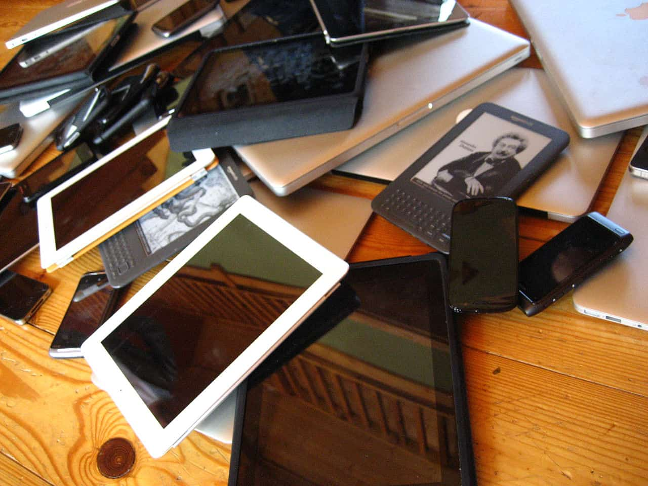 A pile of mobile devices including smart phones, tablets, laptops and ebook readers.