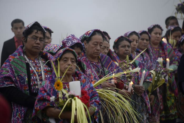Women in Mayan dress along the procession route.