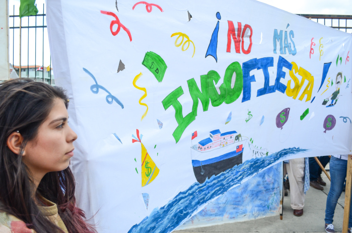 "An anti-shark finning protester holds a sign reading ""Incofiesta."""