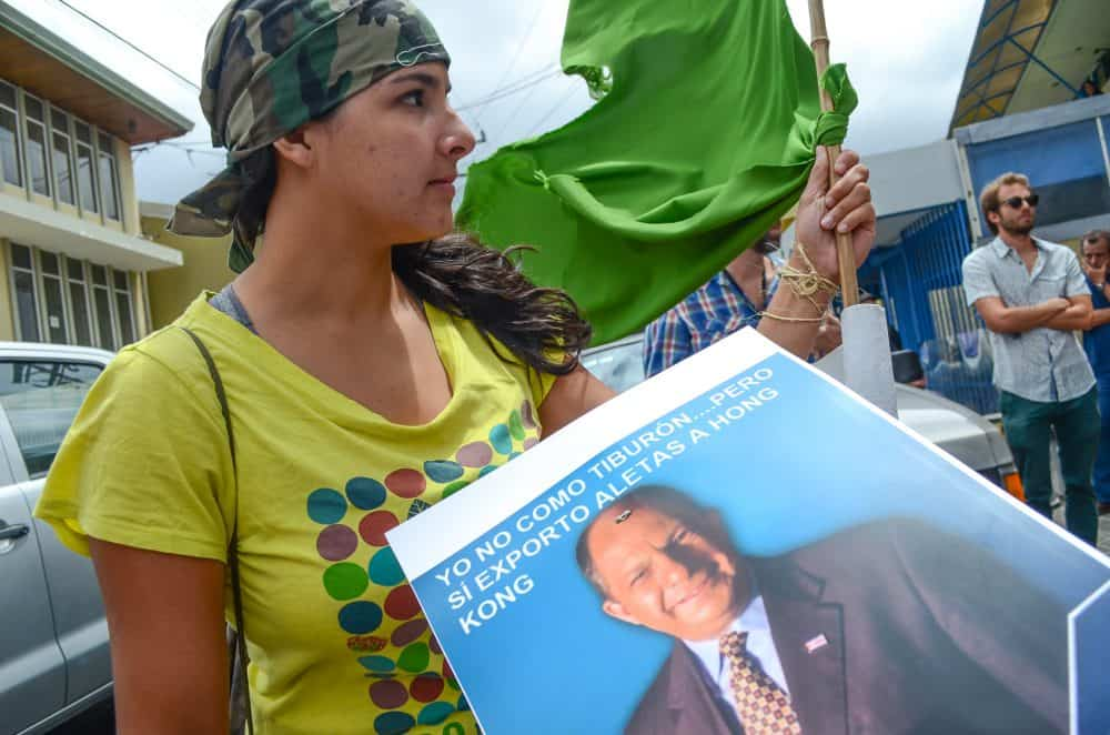 Shark Enemy of the Year: A protester holds a sign of President Luis Guillermo Solís.