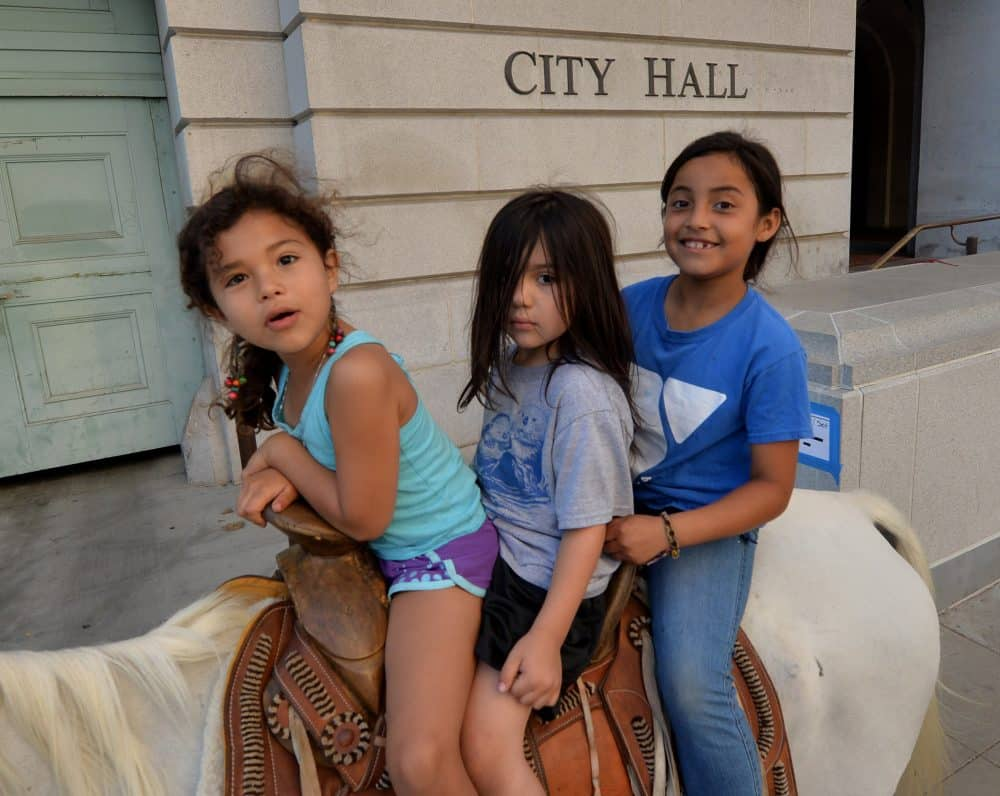 """Immigrant children ride a horse past City Hall during a march in Los Angeles as part of the 300-mile """"Trail for Humanity'' on Aug. 13, 2014."""