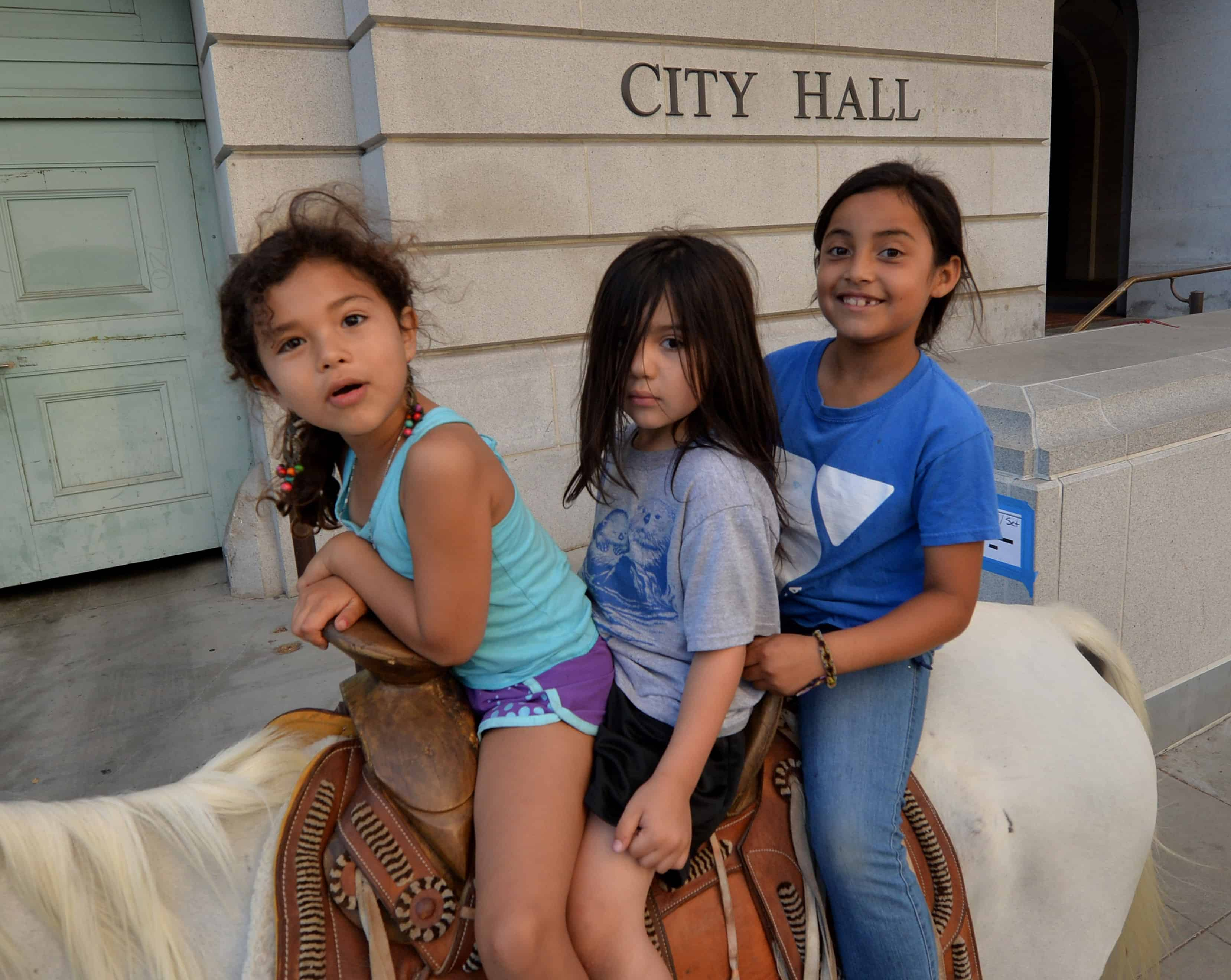 "Immigrant children ride a horse past City Hall during a march in Los Angeles as part of the 300-mile ""Trail for Humanity'' on Aug. 13, 2014."