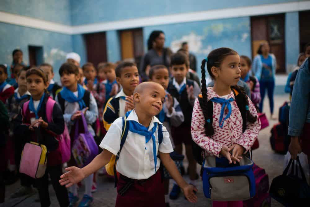 At Manuel Valdes Rodriguez Municipal Primary School in Havana, second grader Kevin Gonzalez throws his arms wide as the children line up before classes and sing patriotic songs, Jan. 26, 2015 .