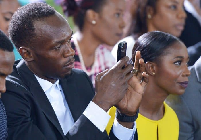 Jamaican sprinter Usain Bolt and sprinter Shelly-Ann Fraser-Pryce watch U.S. President Barack Obama speak.
