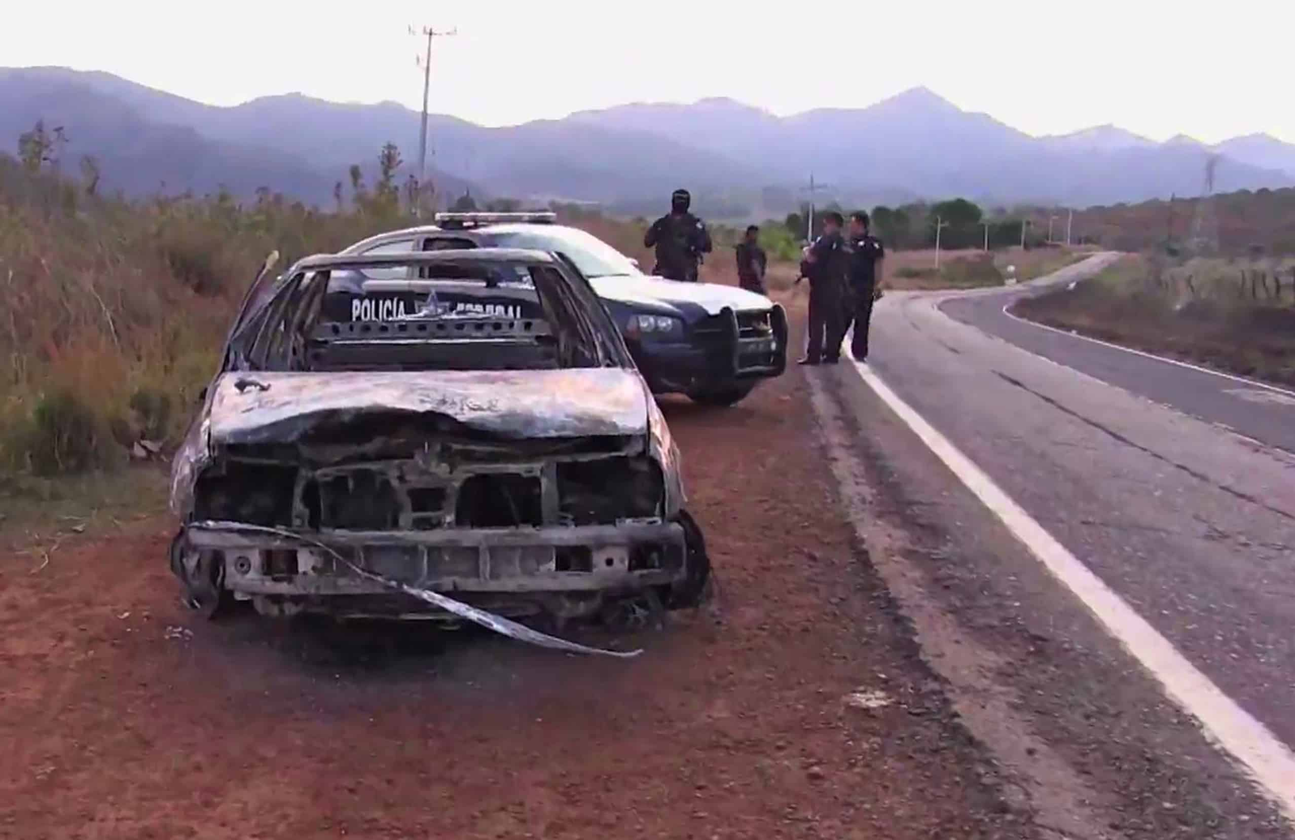 "Grab taken from a video of policemen inspecting a burnt police vehicle on April 7, 2015 on a Jalisco state road, Mexico, where at least 15 police officers were killed in an ambush carried out by a gang called ""Jalisco New Generation Drug Cartel."""