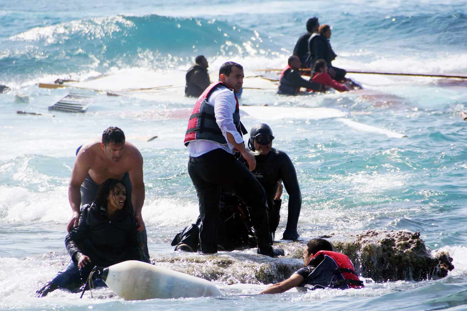 Local residents and rescue workers help a migrant woman after a boat carrying migrants sank off the island of Rhodes, southeastern Greece, on April 20, 2015.