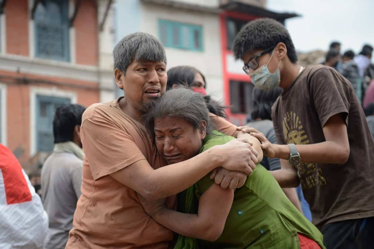 A Nepalese man and woman hold each other in Kathmandu's Durbar Square, a UNESCO World Heritage Site that was severely damaged by an earthquake on April 25, 2015.