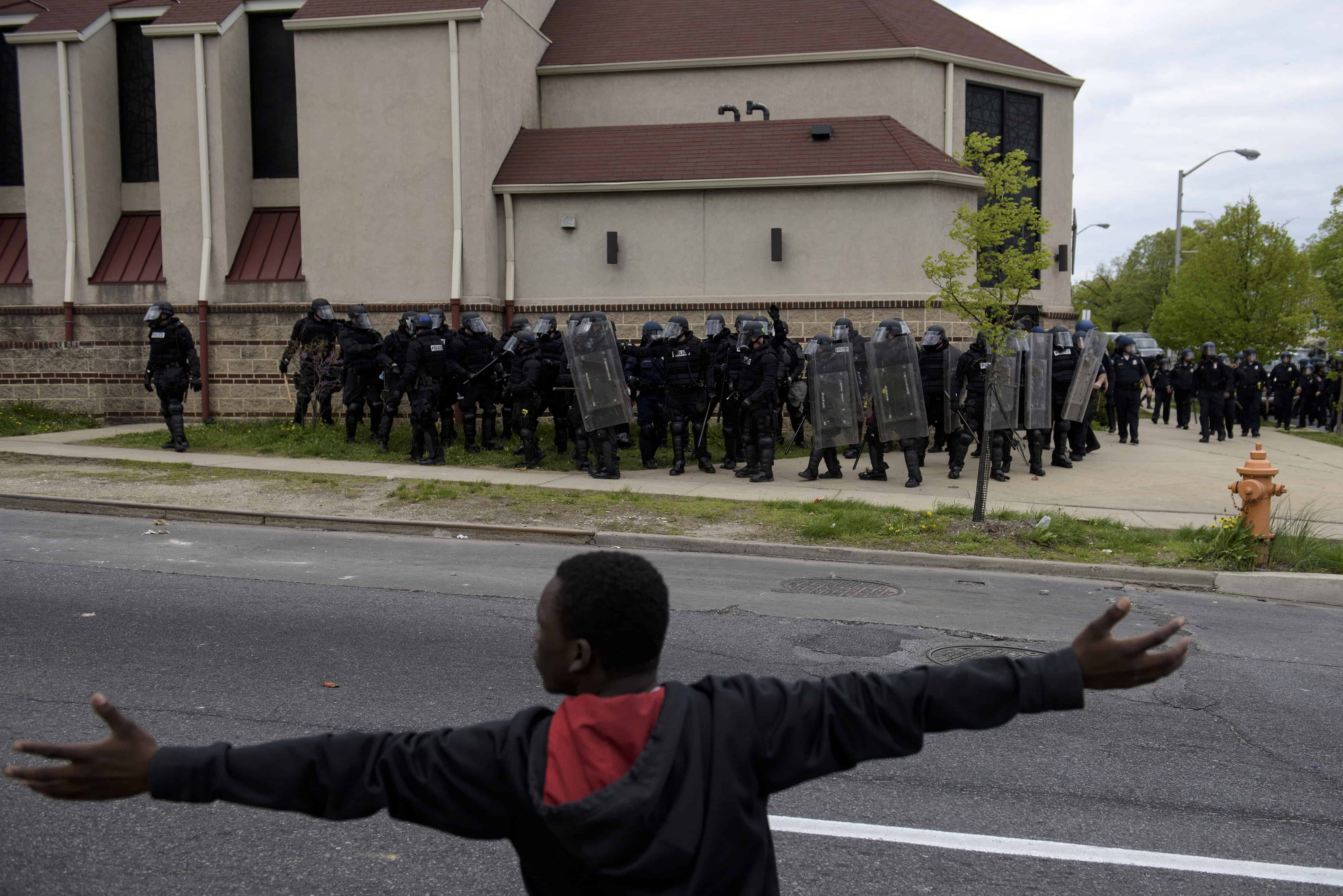 A protester gestures before riot police on April 27, 2015 in Baltimore, Maryland.