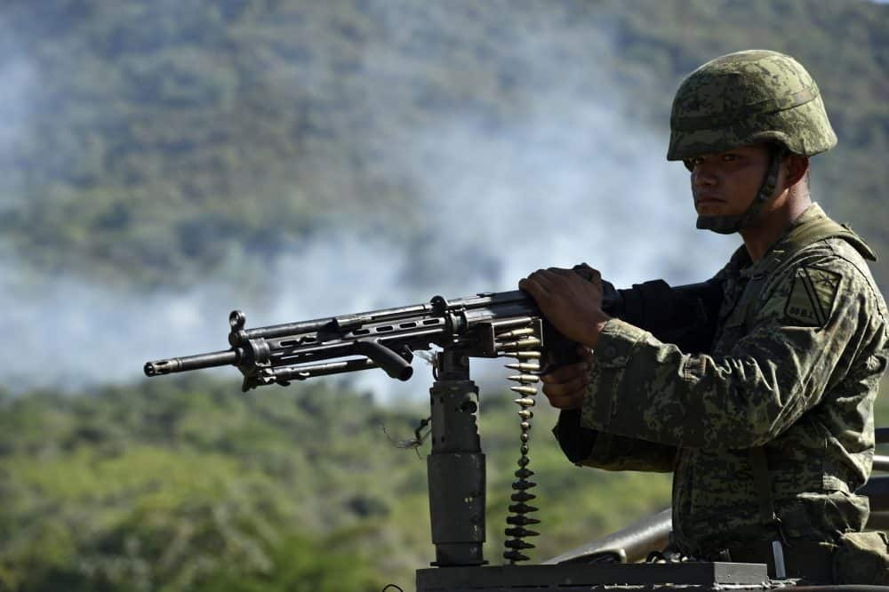 A soldier of the 88th infantry brigade patrols where a military helicopter was shot down in Villa Vieja community, Jalisco, Mexico on May 2, 2015.