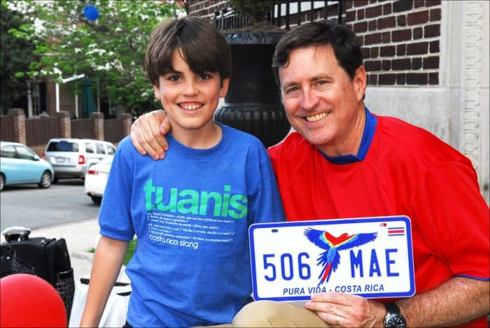 Román Macaya, Costa Rica's ambassador to the United States, and his 10-year-old son, also named Román, hold up a souvenir license plate for sale.