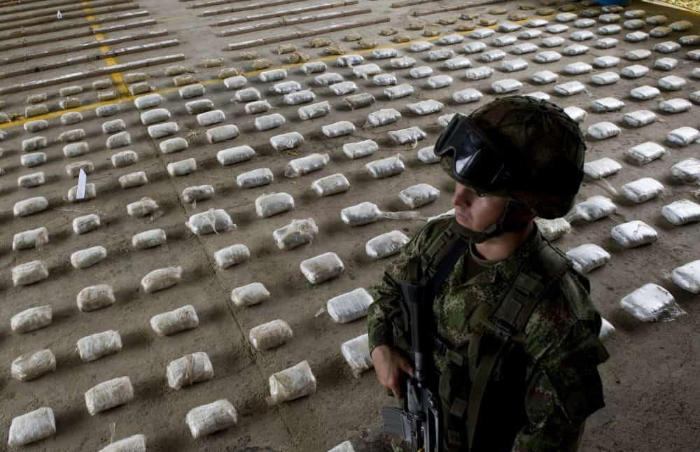 A Colombian soldier stands next to packages of seized cocaine.