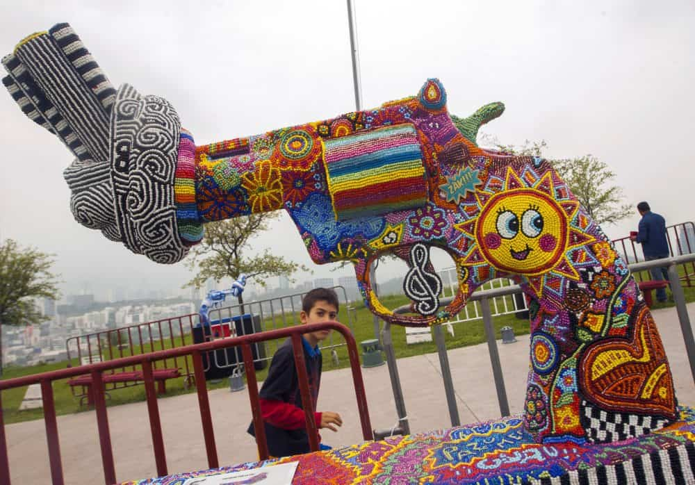 """A boy looks at one of the sculptures of an exhibition called """"Guns for Peace"""" at Bishopric Hill in Monterrey, Nuevo León, Mexico."""