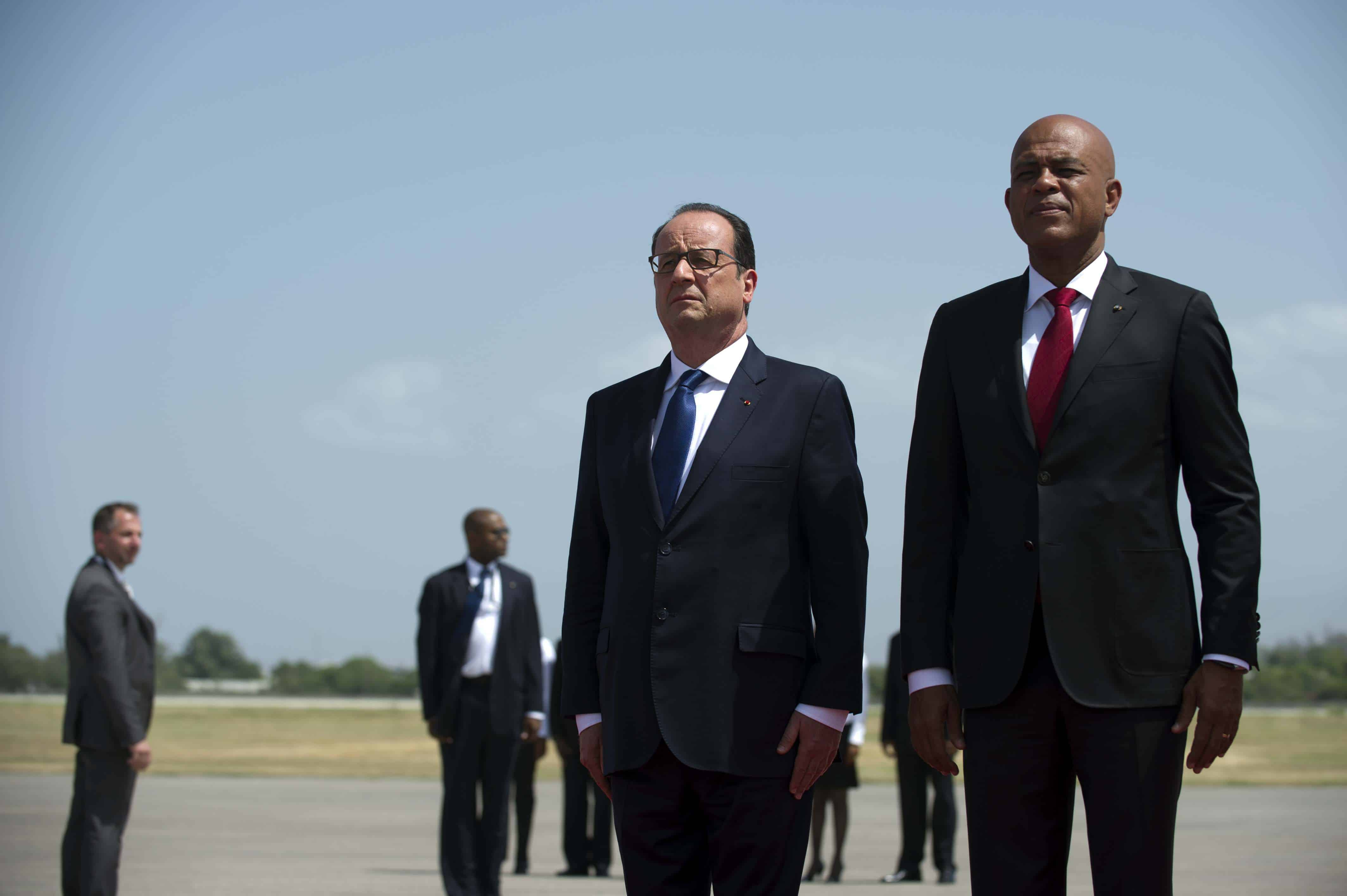 French President Francois Hollande, center, is received by Haitian President Michel Martelly.