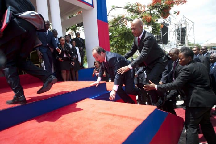 Haitian President Michel Martelly, right, assists French President Francois Hollande, who missed a step at official ceremonies, in Port-au-Prince, Haiti, on May 12, 2015.