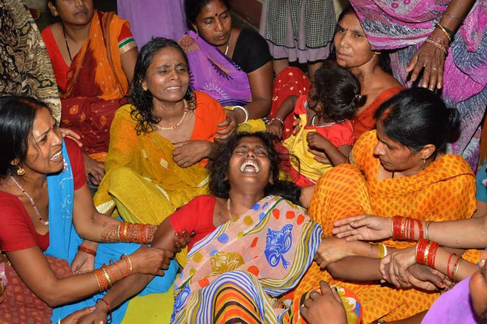 An Indian widow is comforted by relatives and friends.