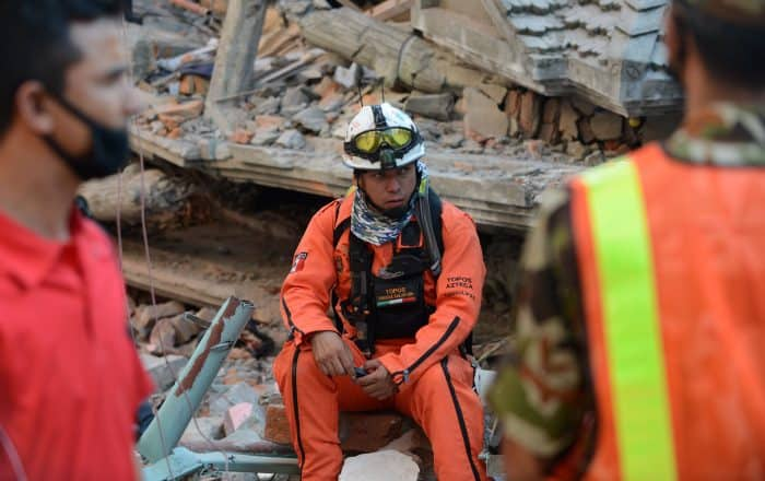Rescue team officials, including one man from Mexico, center, look on during a search.
