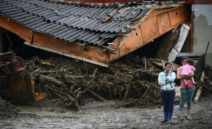 Residents stand next to rubble after a landslide in Salgar Municipality, Antioquia, Colombia, on May 19, 2015.