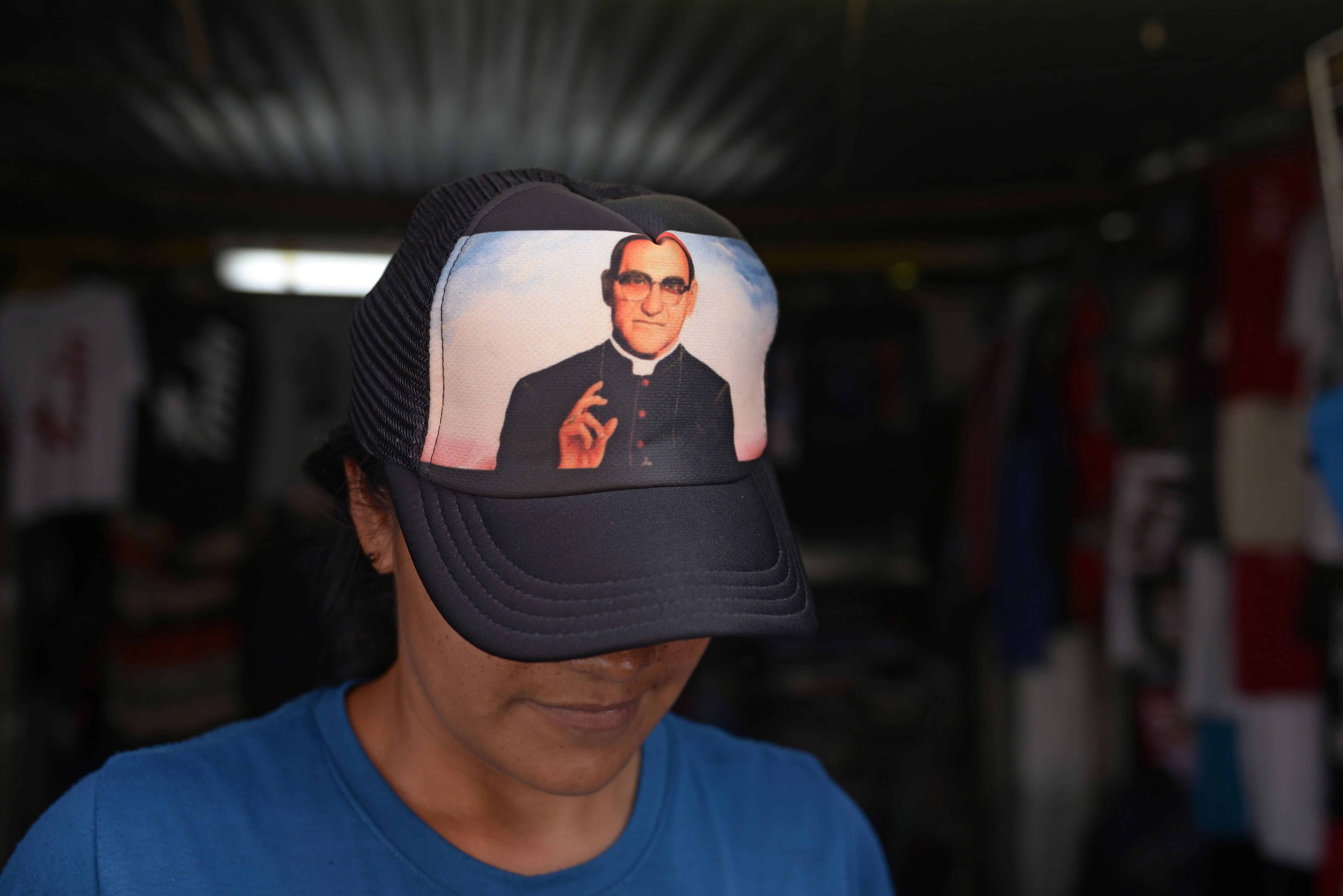A vendor wears a cap with the portrait of Salvadorean Monsignor Oscar Romero (1917-1980) in San Salvador on May 19, 2015. Monsignor Romero will be beatified next May 23.