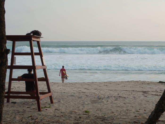 A Santa Teresa lifeguard stands at the water's edge.