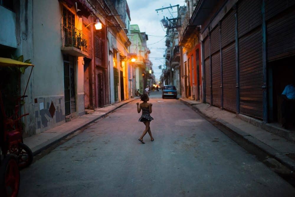 A young girl walks down San Ignacio street in Old Havana as the sun sets.