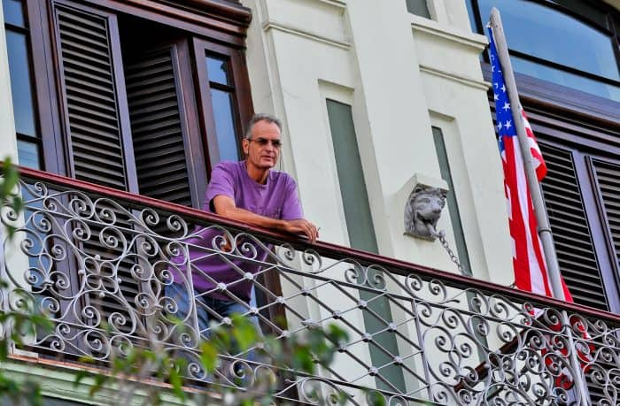 A tourist from the United States looks down from a balcony at the Saratoga Hotel in Havana.