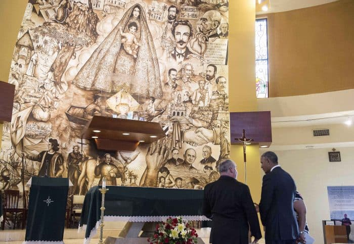 U.S. President Barack Obama speaks with Father Juan Rumin Dominguez as he visits the Shrine of Our Lady of Charity in Miami.