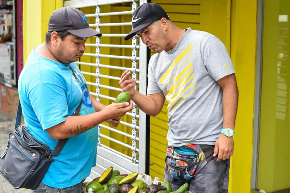 An avocado seller tries hard to convince a customer to buy his product in San José.