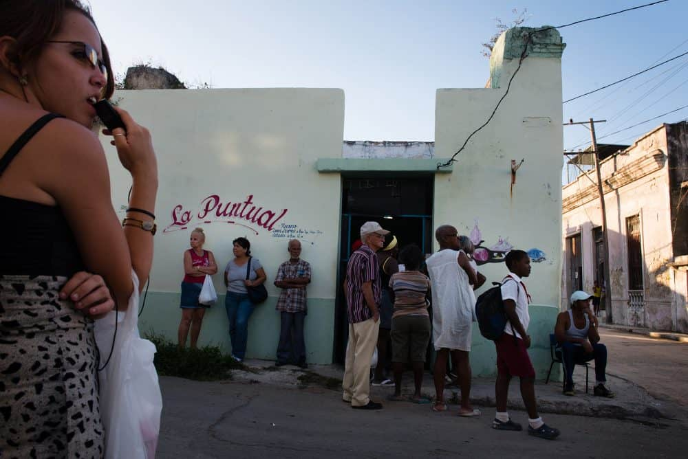 In the Cuban area of Regla, across the bay from Havana, people wait hours for their government ration of chicken.